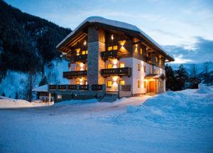 Hell beleuchteter Berghof in der Abenddämmrung