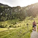 Ein Pärchen beim Wandern durch Gebirge von Saalbach Hinterglemm